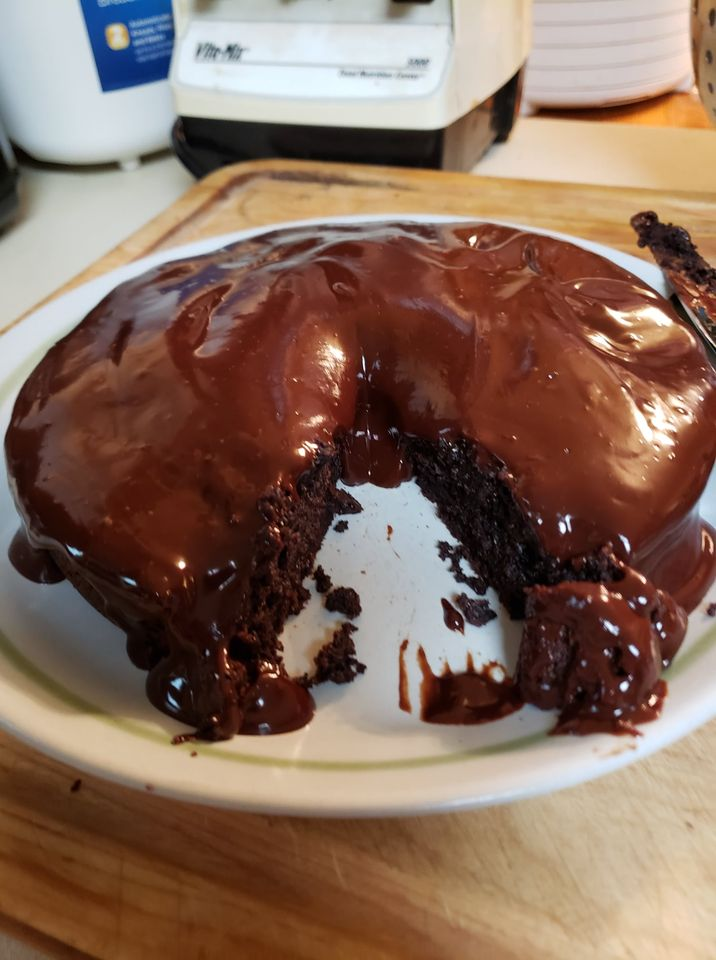 An image of a flourless chocolate cake covered with dark chocolate ganache and with a slice taken out showing how moist the cake is inside.